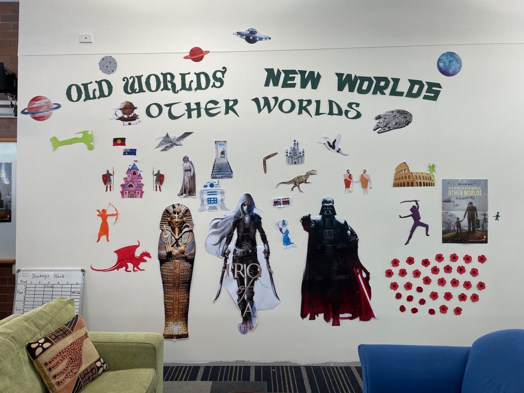 Book characters on a wall with words Old Worlds New Worlds Other Worlds in dark green