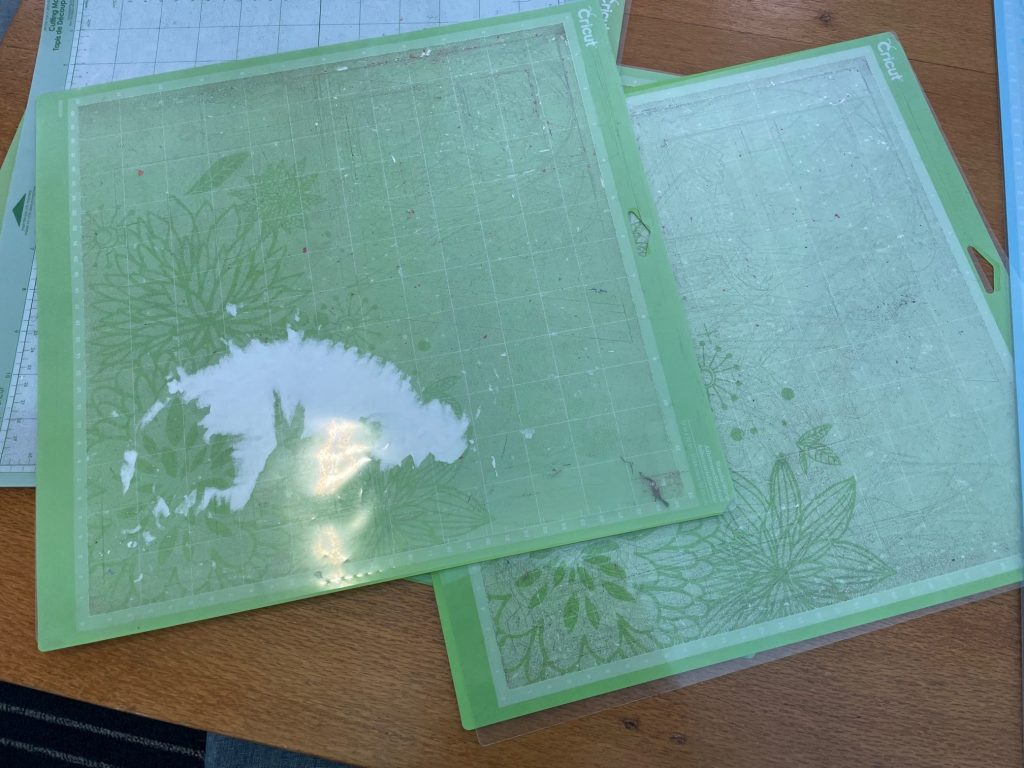 Cricut mats in green with paper stuck on them